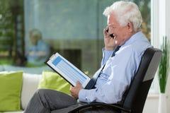 Пожилой бизнесмен работая дома стоковое изображение rf