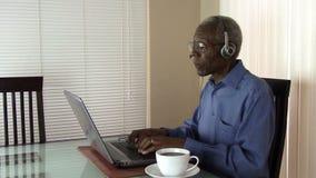 Пожилой гражданин работая на компьтер-книжке дома в Аризоне акции видеоматериалы
