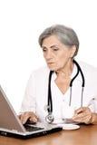 Пожилой доктор женщины работая с компьтер-книжкой Стоковые Фотографии RF