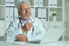 Пожилой доктор с компьтер-книжкой Стоковые Фотографии RF