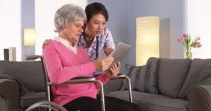 Пожилой пациент и азиатская медсестра имея потеху с таблеткой Стоковая Фотография RF