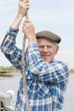 Пожилой рыболов тянуть веревочку Стоковые Фотографии RF