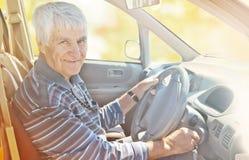 Пожилой усмехаясь человек за рулем День осени солнечный Стоковая Фотография