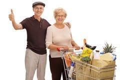 Пожилой человек давая большой палец руки вверх и пожилую женщину с магазинной тележкаой Стоковое Фото