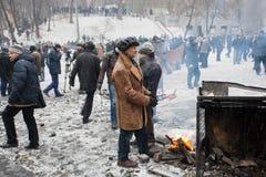 Пожилой человек в огне ожога пальто около баррикад на идя снег улице во время 2 месяцев антипровительственного протеста Euromaidan стоковое изображение rf