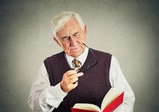 Пожилой человек держа книгу, стекла имея проблемы зрения Стоковые Изображения RF