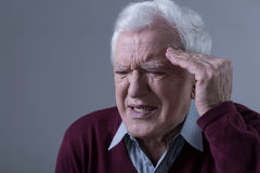Пожилой человек имея головную боль Стоковое Изображение