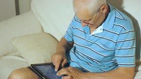 Пожилой человек использует таблетку видеоматериал