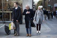 Пожилой человек и молодой человек идя пересечь дорогу В Лондоне, ветреном Стоковая Фотография