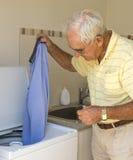 Пожилой человек кладя рубашку в стиральную машину Стоковое Изображение RF