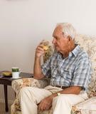 Пожилой человек наслаждаясь чаем утра Стоковые Изображения