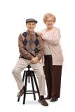 Пожилой человек сидя на стуле с пожилым положением женщины Стоковые Фотографии RF