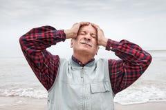 Пожилой человек страдая от головной боли на предпосылке моря Стоковое фото RF