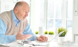 Пожилой человек с компьтер-книжкой Стоковые Фото
