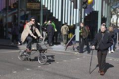Пожилой человек с крестом тросточки дорога, пока молодой человек в модном пальто ехать велосипед Стоковые Изображения