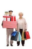 Пожилой человек с настоящими моментами и пожилая женщина с хозяйственными сумками Стоковое Фото