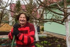 Пожилой человек с садовым инструментом дает подсказки и фокусы для работы Стоковое фото RF