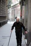 Пожилой человек с тросточкой, близко парикмахерами Стоковое Фото