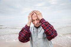 Пожилой человек терпя от головной боли на предпосылке моря Стоковая Фотография RF