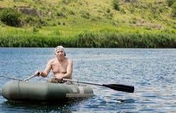Пожилой rowing рыболова через озеро Стоковые Изображения