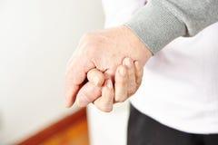Пожилые гражданины держа их руки Стоковые Изображения