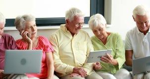 Пожилые гражданины используя цифровые таблетку и компьтер-книжку видеоматериал