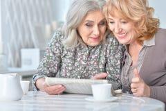Пожилые женщины читая газету Стоковые Изображения