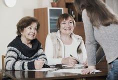 Пожилые милые положительные женщины делая будут на общественной нотариальной конторе Стоковая Фотография