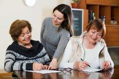 Пожилые милые усмехаясь женщины делая будут на нотариальной конторе Стоковое фото RF