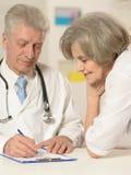 Пожилые доктора на таблице Стоковое Изображение