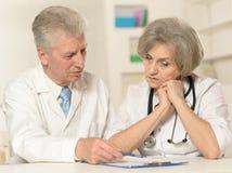 Пожилые доктора на таблице Стоковая Фотография