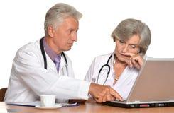 Пожилые доктора с компьтер-книжкой Стоковое Изображение