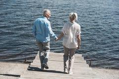 Пожилые пары держа руки и идя на берег реки на дневном времени Стоковая Фотография