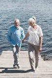 Пожилые пары держа руки и идя на берег реки на солнечном дне Стоковое Изображение