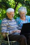 Пожилые пары имея потеху с компьтер-книжкой outdoors Стоковые Изображения RF