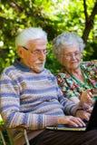 Пожилые пары имея потеху с компьтер-книжкой outdoors Стоковое фото RF
