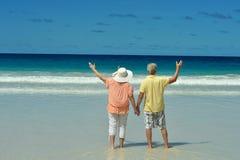 Пожилые пары идя вдоль seashore стоковое изображение