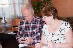 Пожилые пары на таблице с тетрадью Стоковые Фото