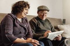 Пожилые пары читая газету Стоковое Фото