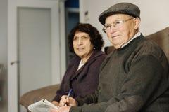 Пожилые пары читая газету Стоковые Фотографии RF