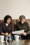 Пожилые пары читая газету Стоковое Изображение RF
