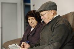 Пожилые пары читая газету Стоковая Фотография