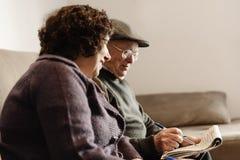 Пожилые пары читая газету Стоковые Изображения RF