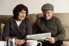 Пожилые пары читая газету Стоковое Изображение
