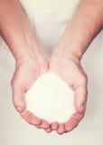 Пожилые руки держа каменную соль Стоковое Изображение RF