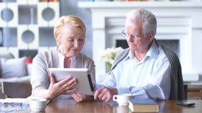 Пожилые счастливые пары работая на таблетке в современной квартире акции видеоматериалы