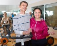 Пожилые человек и женщина в велосипедах предпосылки на спортзале Стоковые Изображения RF