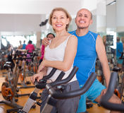 Пожилые человек и женщина в велосипедах предпосылки на спортзале Стоковое Изображение