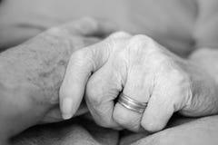 Пожилые люди держа руки Стоковая Фотография