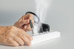 Пожилые люди имеют затыкать ошибки проблемы электрический Стоковые Изображения